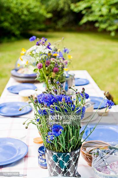 Flower vase and plates arranged on dining table