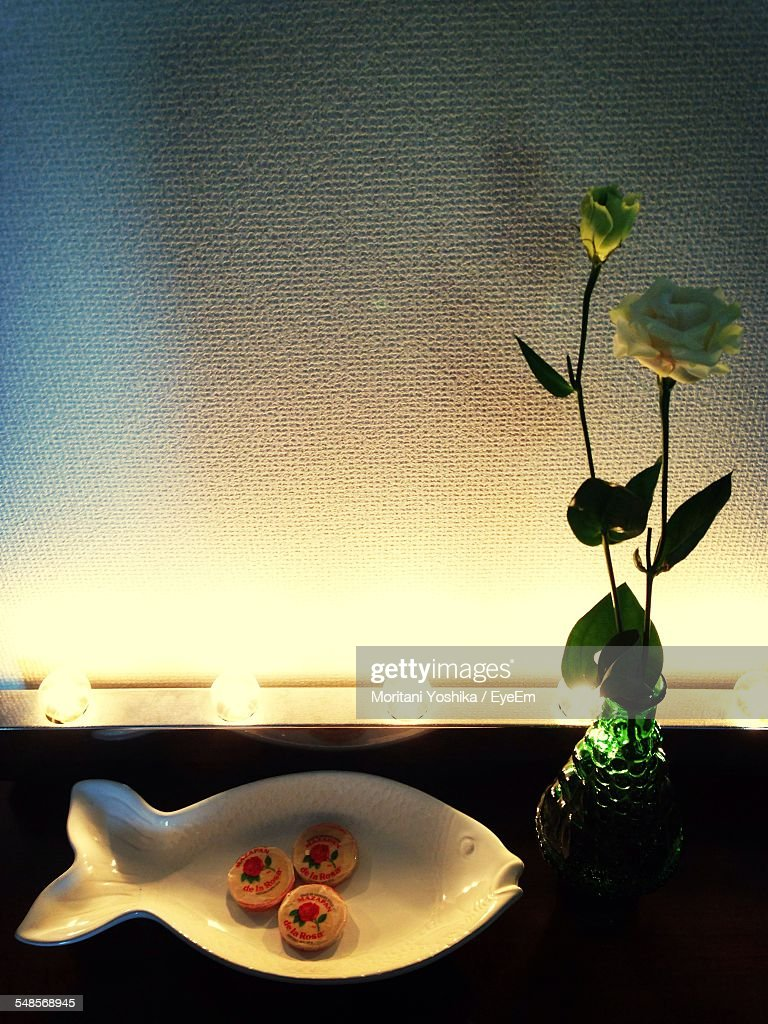Flower vase by fish bowl on illuminated table stock photo getty flower vase by fish bowl on illuminated table reviewsmspy