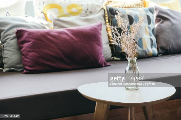 flower vase on table by pillows on sofa at home - cushion stock photos and pictures