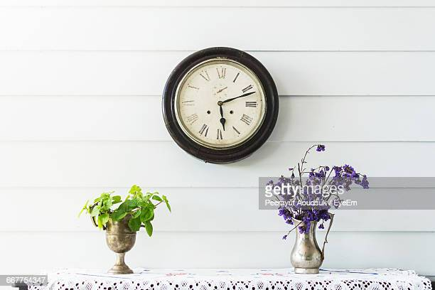 Flower Vase On Table With Clock Mounted On Wall At Home