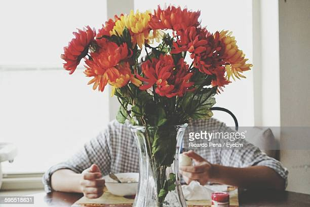 flower vase on table with man having breakfast at home - obscured face stock pictures, royalty-free photos & images