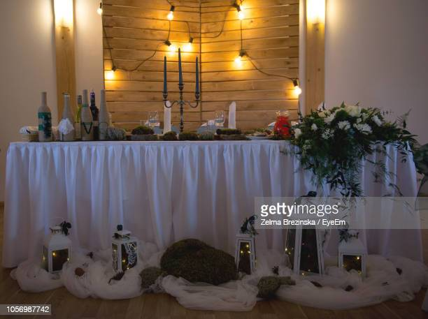 Flower Vase With Lanterns On Table In Illuminated Room