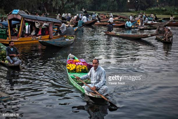A flower vendor waits for customer as other Kashmiri men remain busy in buying and selling vegetables at the floating vegetable market on Dal Lake at...