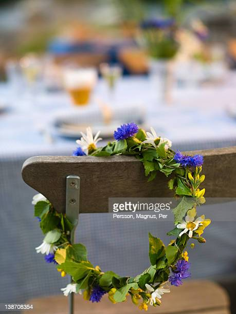 flower wreath hanging on chair - midsommar stock pictures, royalty-free photos & images