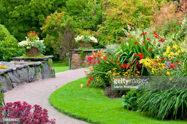 flowerbeds, flowerpots and stone wall - landscaped stock pictures, royalty-free photos & images