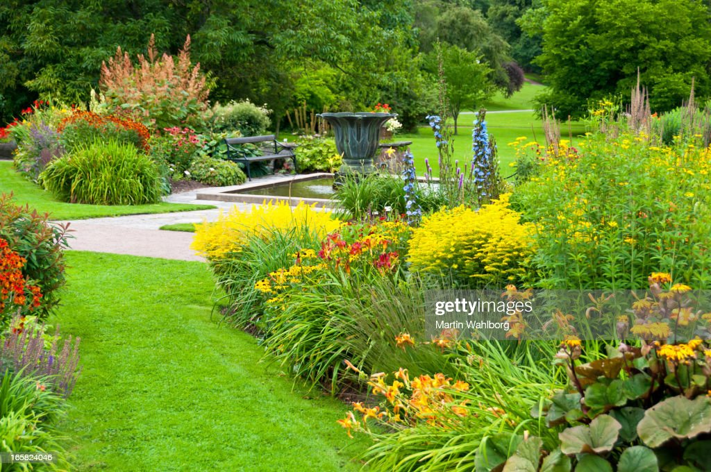 Flowerbeds, lawn and pond in a beautiful park : Stock Photo