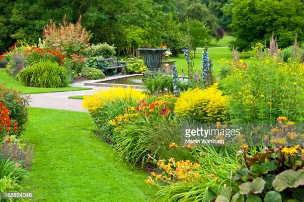 flowerbeds, lawn and pond in a beautiful park - botanical garden stock pictures, royalty-free photos & images