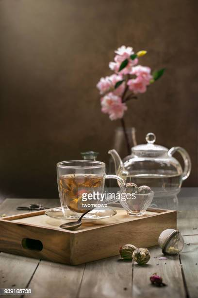 flowering green tea in glass drinking glass. - steeping stock pictures, royalty-free photos & images