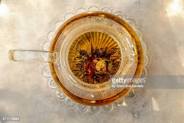 flowering tea pod in glass tea pot taken from above - steeping stock pictures, royalty-free photos & images