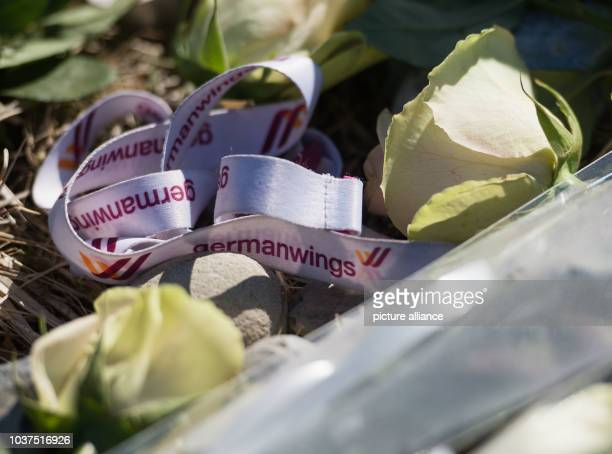 Flowers and a keychain which reads 'Germanwings' are placed around a memorial stele for the victims of Germanwings flight 4U 9525 in La Vernet France...
