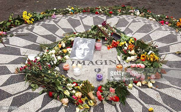 Flowers and a photo of musician John Lennon lie at the Strawberry Fields memorial December 11 2005 in New York City Lennon was shot and killed...