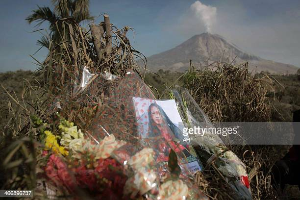Flowers and a portrait of a victim killed during the eruption of Mount Sinabung volcano are left by relatives on a hill in Karo district overlooking...