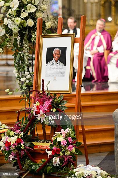 Flowers and a portrait of late Nelson Mandela are seen at a remembrance service for the former South African president at the Saint Michael and St...