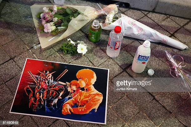 Flowers and a poster with anime characters are placed at a cross road where seven people were stabbed to death and 10 people were injured in a...