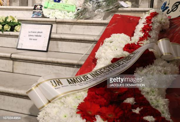 Flowers and a sign reading 'France cries for Johnny and me too' are displayed during a mass in tribute to French rock singer Johnny Hallyday in Paris...