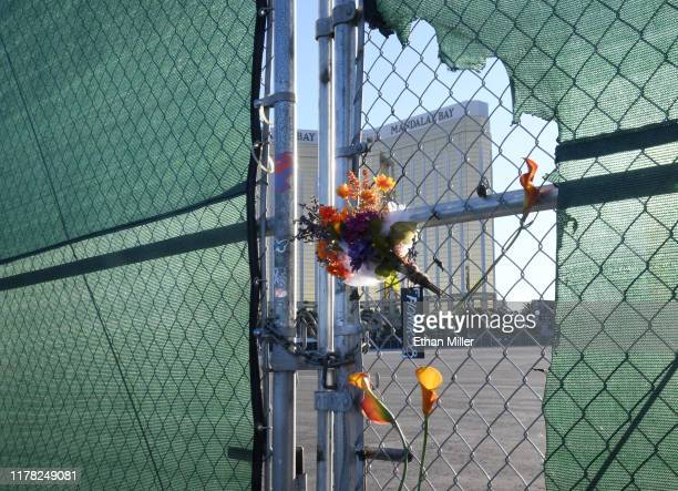 Flowers and a sign reading HONOR 58 hang on a fence outside the Las Vegas Village across from Mandalay Bay Resort and Casino as a tribute to those...