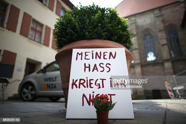 """Flowers and a sign reading """"you don't get my hate"""" stand in Ansbach, southern Germany, on July 26, 2016 two days after a Syrian asylum seeker blew..."""