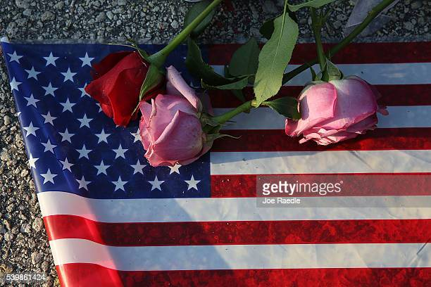 Flowers and an American flag are seen on the ground near the Pulse Nightclub where Omar Mateen allegedly killed at least 50 people on June 13 2016 in...