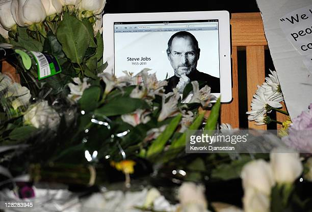 Flowers and an iPad showing a picture of Steve Jobs are placed at a makeshift memorial for Steve Jobs at the Apple headquarters on October 5 2011 in...