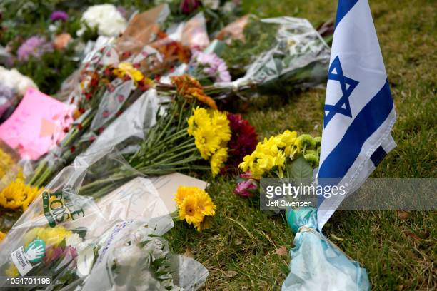 Flowers and an Israeli flag sit at a makeshift memorial down the street from the site of the mass shooting that killed 11 people and wounded 6 at the...