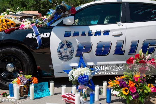 TOPSHOT Flowers and candles adorn a memorial outside the Dallas Police Headquarters on July 8 2016 The gunman who opened fire on Dallas officers...