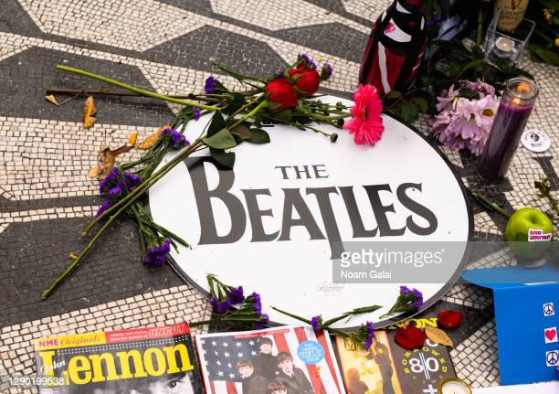"Flowers and candles are left by The Beatles drumhead on the ""Imagine"" memorial in honor of John Lennon on the 40th anniversary of his death at..."