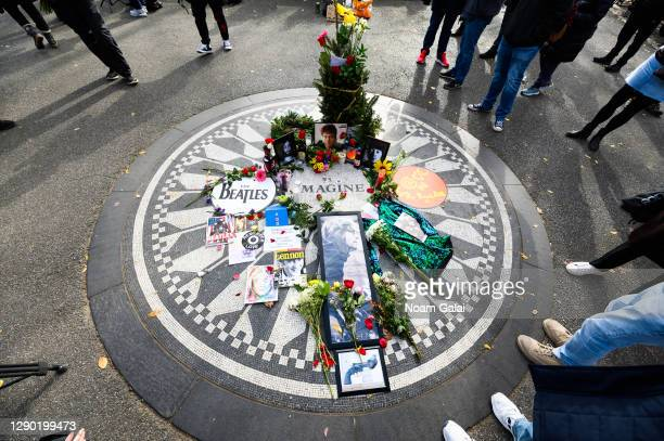 "Flowers and candles are left on the ""Imagine"" memorial in honor of John Lennon on the 40th anniversary of his death at Strawberry Fields in Central..."