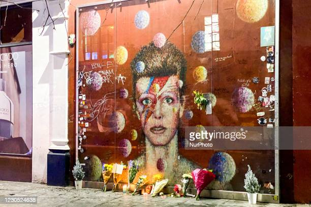 Flowers and candles are left past a mural depicting the cover of Aladdin Sane, to remember the firth anniversary of the death of the British iconic...