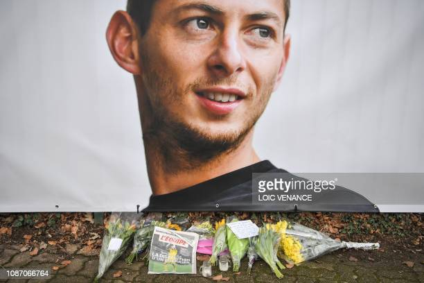TOPSHOT Flowers and candles are left with the front page of French sports daily newspaper 'L'Equipe' reading The disappearance of a warrior next to a...