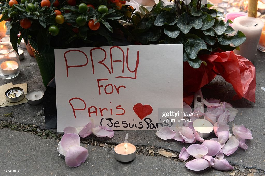 Flowers and candles are pictured at a makeshift memorial near the Bataclan concert hall in Paris on November 15, 2015, two days after a series of deadly attacks. Islamic State jihadists claimed a series of coordinated attacks by gunmen and suicide bombers in Paris on November 13 that killed at least 129 people in scenes of carnage at a concert hall, restaurants and the national stadium.