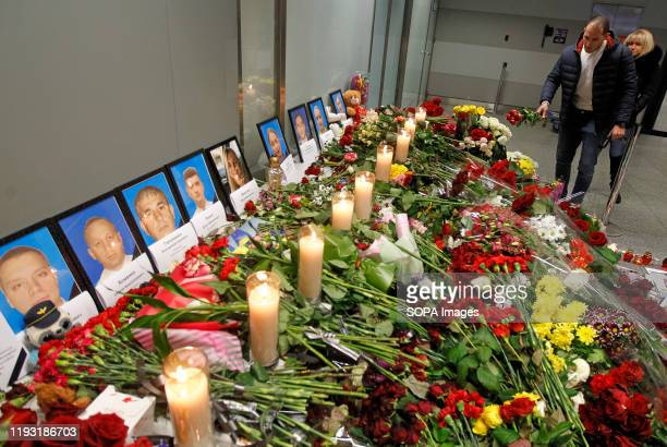 Flowers and candles are placed in front of the portraits of the victims of flight PS 752 at the memorial corner of Boryspil International Airport....