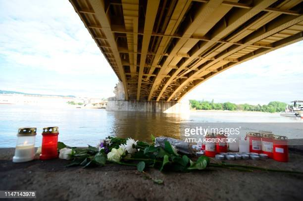TOPSHOT Flowers and candles are placed on the banks of the river Danube in Budapest Hungary on May 31 at the spot of a boat accident with seven dead...