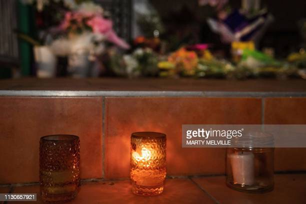 Flowers and candles are placed on the front steps of the Wellington Masjid mosque in Kilbirnie in Wellington on March 15 after a shooting incident at...