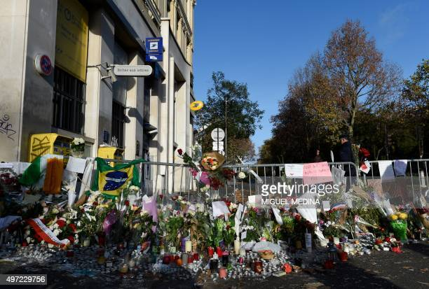 Flowers and candles are seen near the crime scene of the Bataclan concert hall on November 15 2015 in Paris following a series of coordinated attacks...