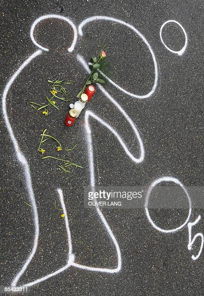 Flowers and candles lay on the chalk outline of the body of a teenager who went on the rampage at his former school the Winnenden Albertville...