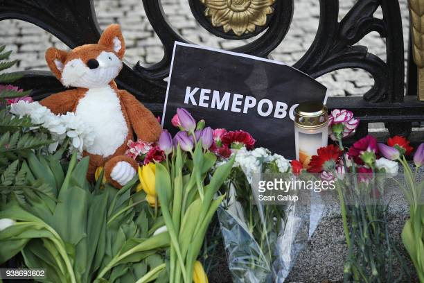 Flowers and candles left by mourners lie at the gate of the Russian Embassy to commemorate the victims of the Kemerovo fire on March 27 2018 in...