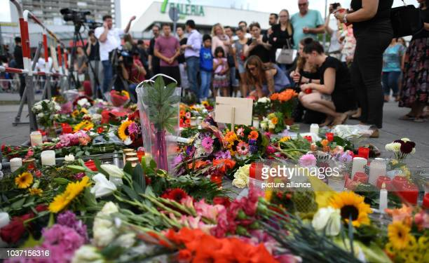 Flowers and candles lie close to the Olympia Einkaufszentrum one day after a shooting with deaths and casualties in the building in MunichGermany 23...