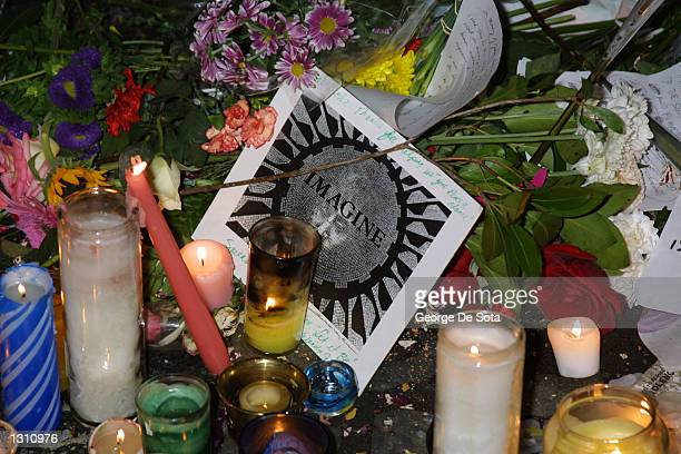 Flowers and candles sit in honor of slain musician John Lennon on the 20th anniversary of his murder December 8 2000 in the Strawberry Fields area of...
