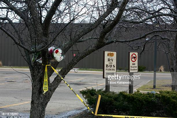 Flowers and crime scene tape hang from a tree in the parking lot of a Cracker Barrel where a gunman went on a shooting rampage, on February 21, 2016...