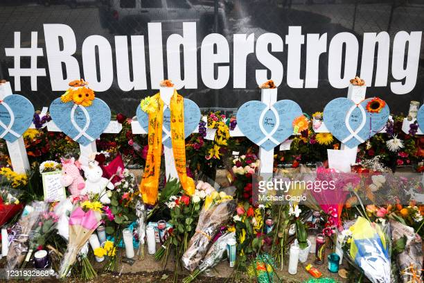 Flowers and crosses sit at a makeshift memorial outside a King Soopers grocery store on March 25, 2021 in Boulder, Colorado. Ten people, including a...