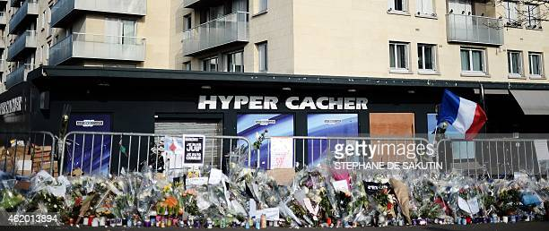 Flowers and messages are laid on January 23, 2015 in front of the Hyper Casher shop in Paris prior a march organised toward the satirical newspaper...