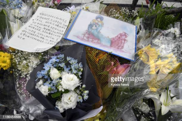 Flowers and messages are placed near the threestory studio of Kyoto Animation Co in Kyoto western Japan on July 19 a day after a man set it on fire...