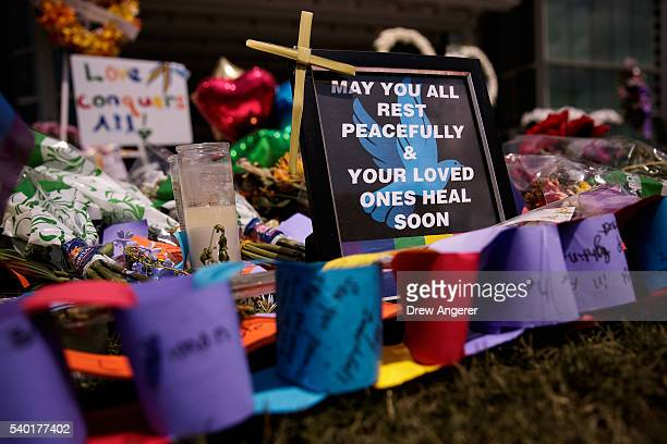 Flowers and messages for the victims of the Pulse Nightclub shooting lay at a makeshift memorial June 14 2016 in Orlando Florida The shooting which...