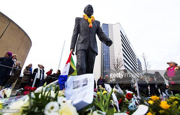 Flowers and messages of condolence are picture in front of a statue of Late South African president Nelson Mandela in The Hague on December 13 2013...