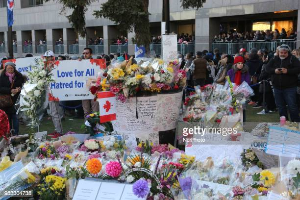 Flowers and messages of condolence at a memorial during an interfaith vigil at Nathan Phillips Square in memory of the 10 people killed and 15 people...