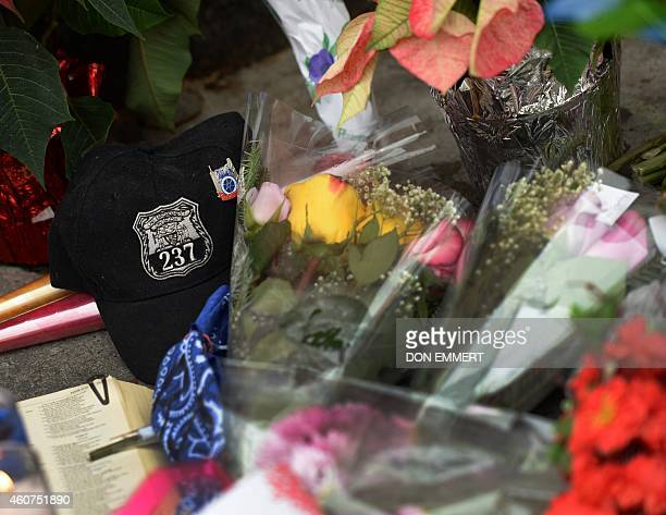 Flowers and momentos are left at a memorial near Tompkins Ave and Myrtle Ave December 21 2014 in New York near the site where two New York City...