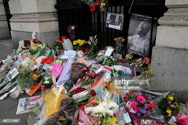 "Flowers and other tributes left outside South Africa House in London following Mandela's death, including a photograph bearing the words ""There is no..."
