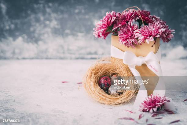 Flowers and painted Easter eggs in a nest