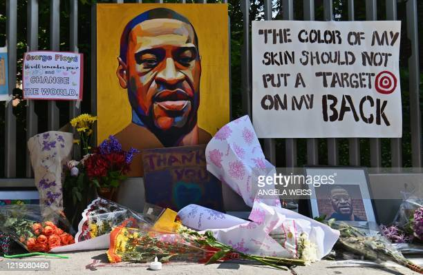 Flowers and painting adorn a tribute to George Floyd in Harlem on June 10 in New York City. - On May 25 Floyd, a 46-year-old black man suspected of...