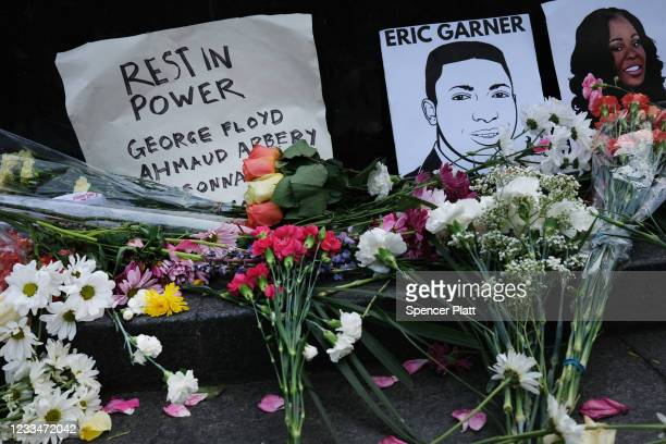 Flowers and pictures lay at a memorial to victims of police violence during a demonstration in front of a Manhattan court house and jail to protest...